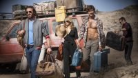 The three main characters carry their luggage from a beat up old car in an arid looking area. Credit: Netflix