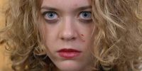 A close-up of Terri in Syzygy, looking with wide eyes and with blood flecked on her face.