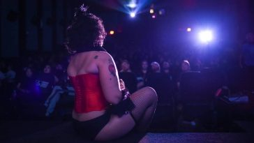 Frank-N-Furter sits on stage and looks out into the audience