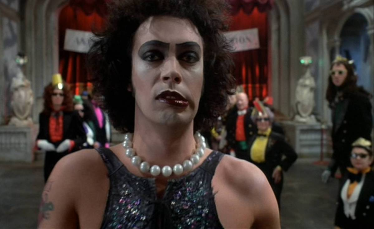 Frank-N-Furter walks towards the camera in the ballroom full of Transylvanians.