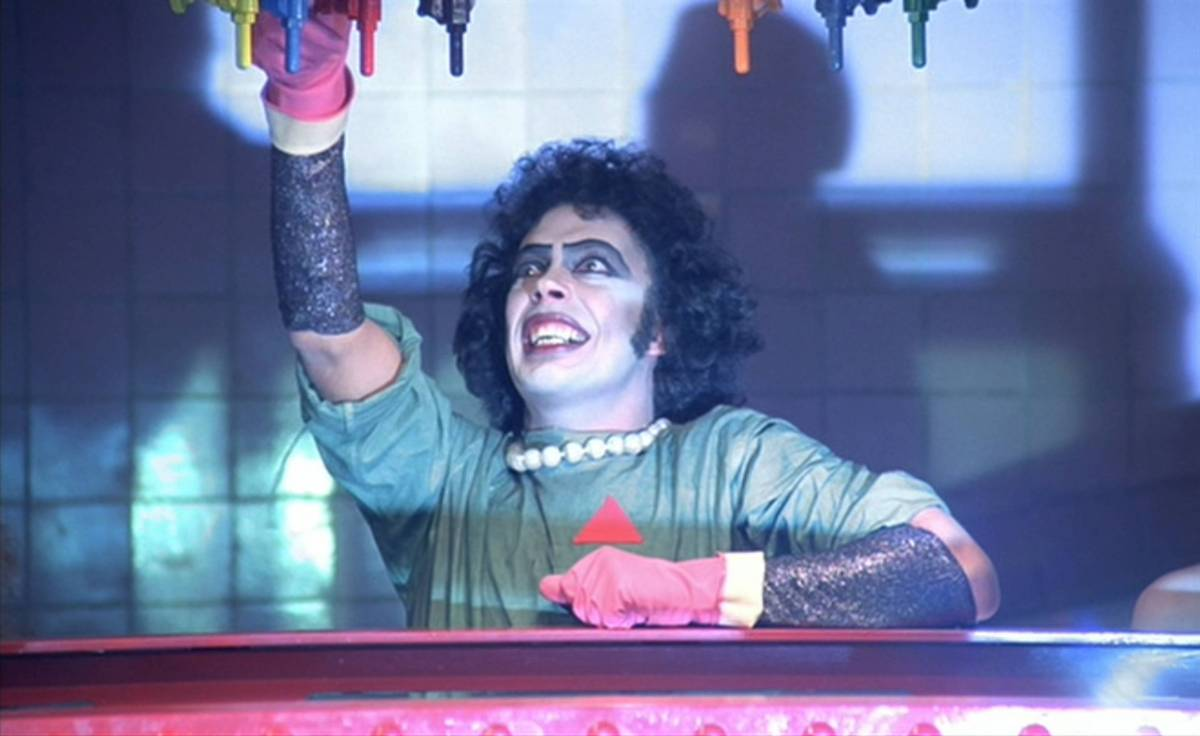 Frank-N-Furter fiddles with lab equipment to bring Rocky to life.
