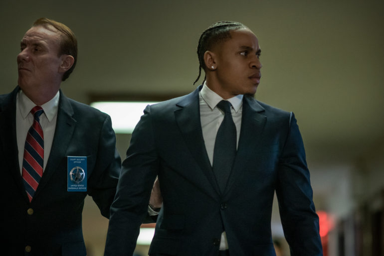 Dre, wearing a suit, is escorted by a police officer