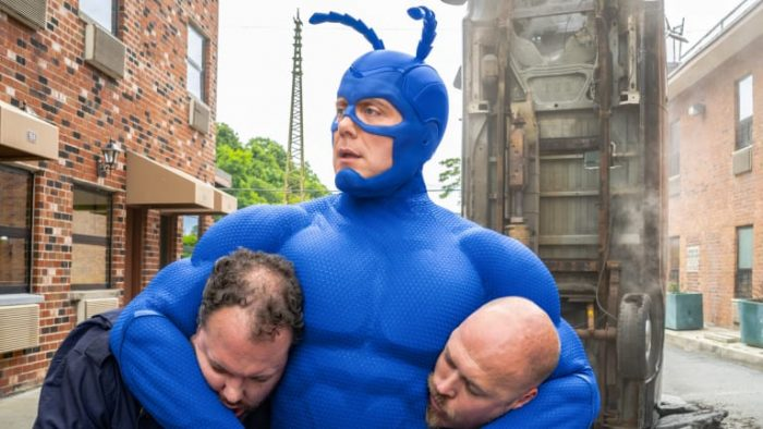The Tick ('16) with two criminals in headlocks with an overturned car in the background