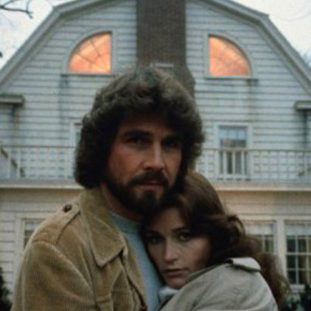 a couple hug tightly in front of the amityville house