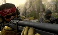 a soldier wearing a red bandana looks down the viewer of his big gun