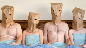 Four people in bed with paper bags over their heads in Baghead.