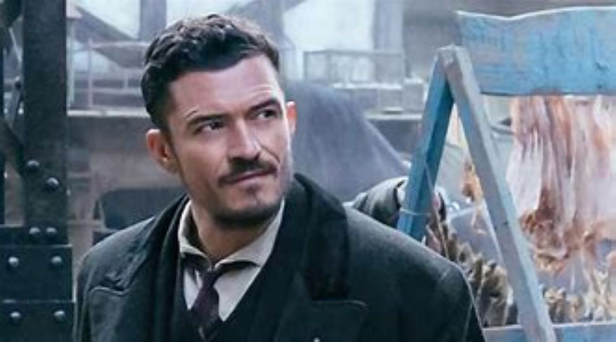 A bruised Philo (Orlando Bloom) stands next to some meat on a market stall in Carnival Row.
