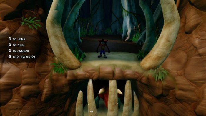 Crash stands facing the player on the second level of a cave overlooking the area.