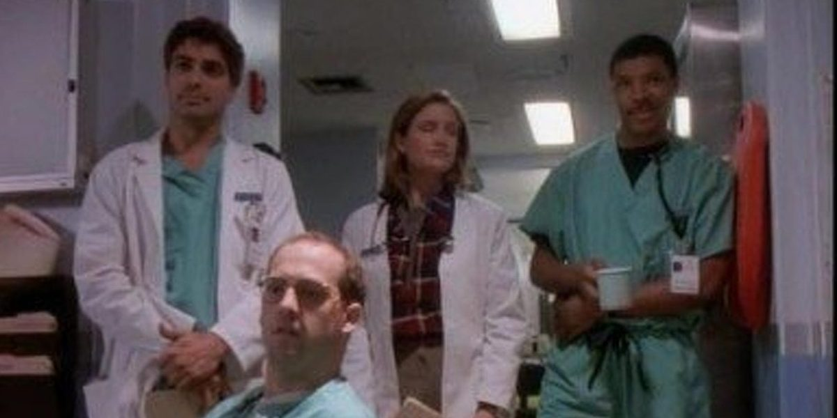Doctors Ross, Lewis and Benton look on in the ER hallway at the new interns, and Doctor Greene looks with them while seated.