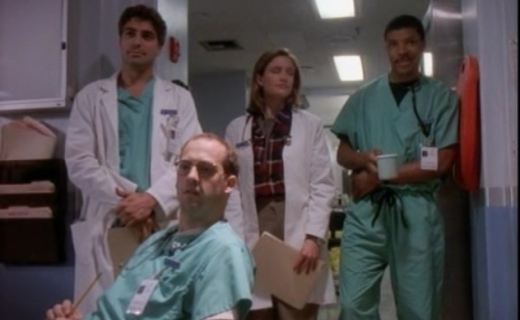 Doctors Greene, Ross, Lewis and Benton look offscreen towards the student doctor's extremely white coat.