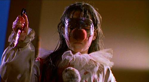 A young girl in a clown costume holds up bloody scissors.