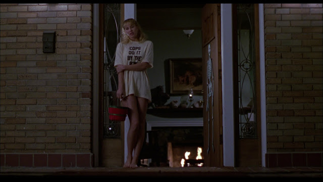 """A teenage girl wearing only a shirt that reads, """"Cops Do It By the Book"""", stands ready to pass out Halloween candy."""