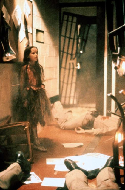 A young girl in a worn out princess costume stands in the middle of a bloodbath at a police station.