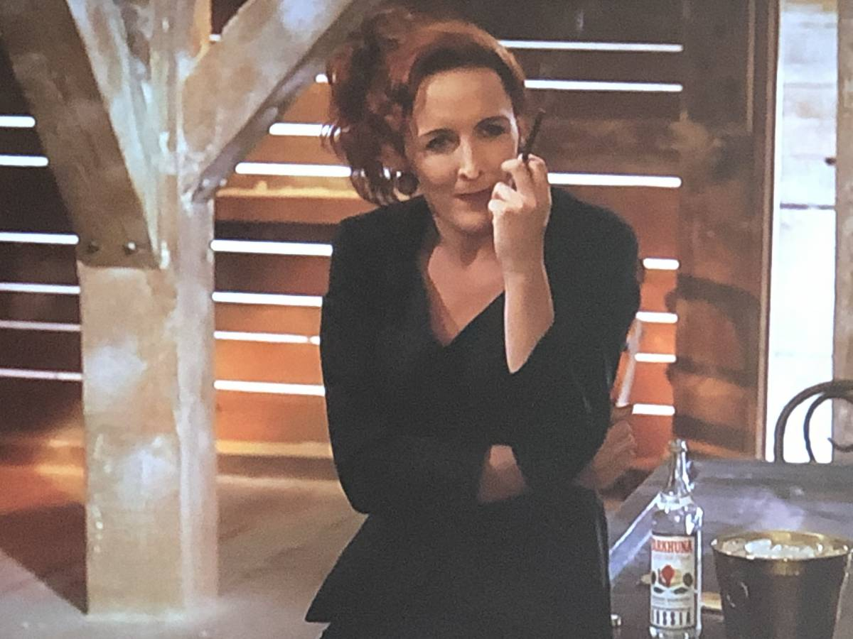 Fiona Shaw as Paulina Novacek, leaning on a desk and smoking a long cigarette