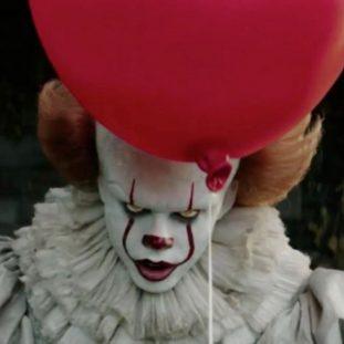 A clown holding a red balloon.