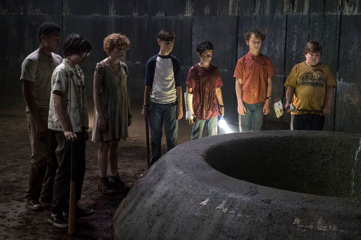 A group of seven children stand around a sewer opening in It Chapter One