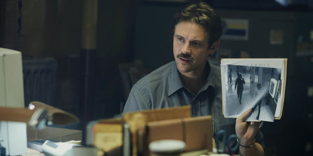 An obsessed detective holds up a still photograph at his desk