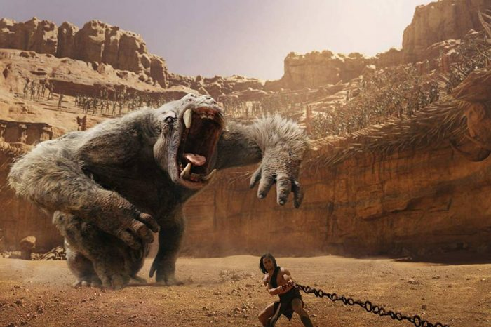 John Carter fights to free himself from his chains before a barrelling white ape