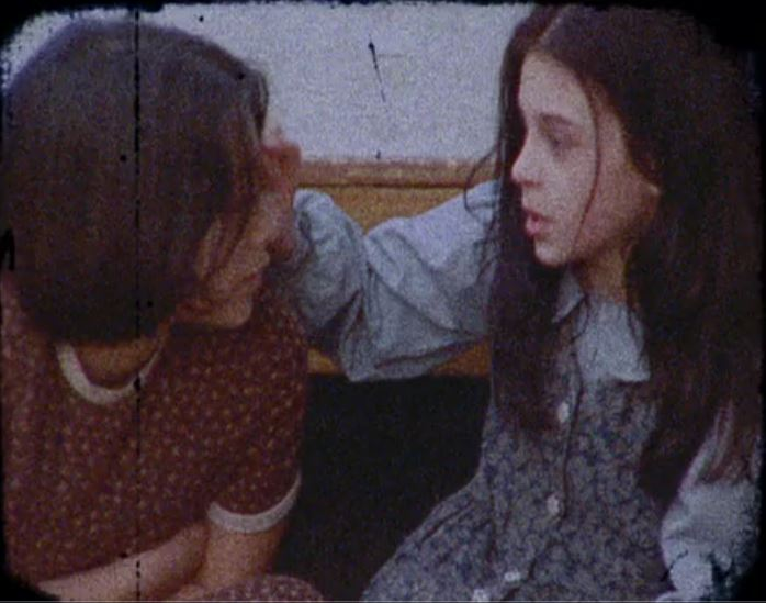 Young Lucie and Anna look at each other and talk quietly