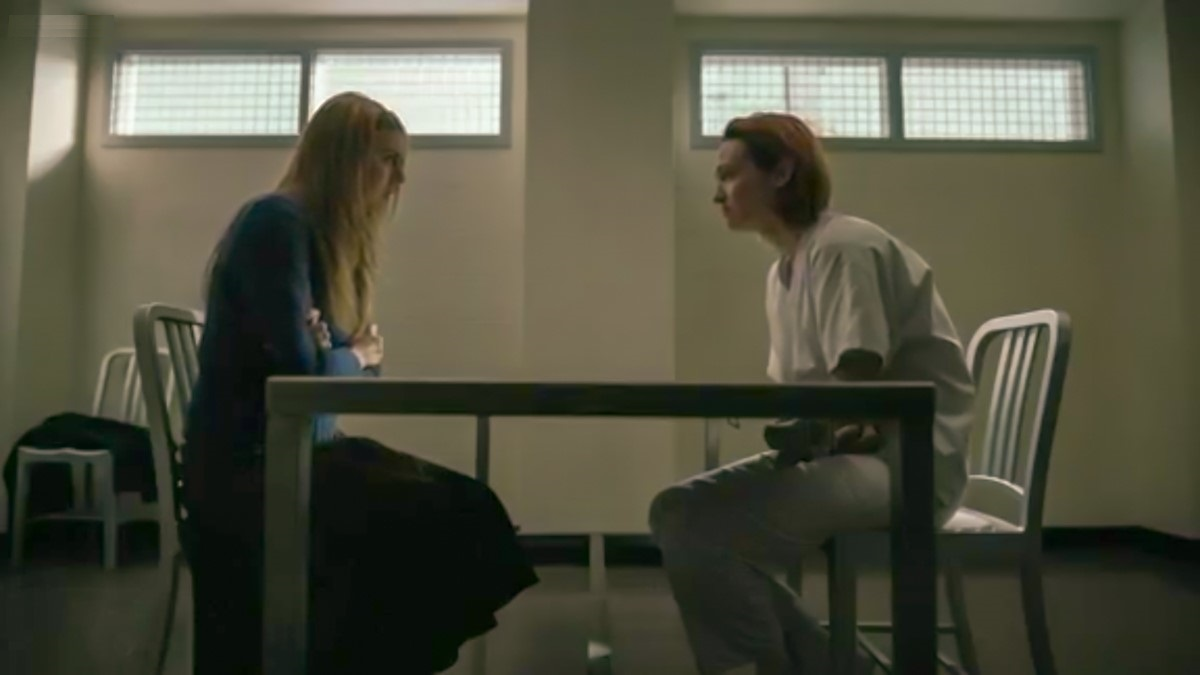 Holly and Lou sit, facing each other, in a stark white hospital room, Holly looks uncomfortable.