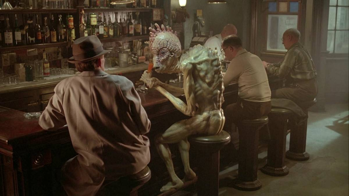 Peter Weller talks to a Mugwump in a bar