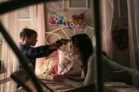 Christopher holds a gun to Emelies head as she lies on a bed