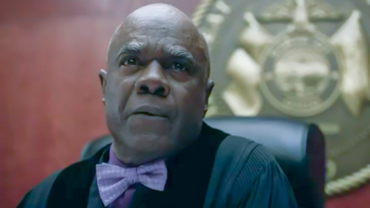 Judge Raines sits at the bench looking out, purple bow tie showing prominently against his block robes