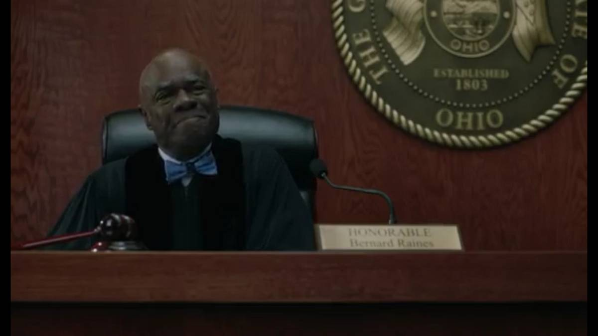Judge Raines, in robes and a blue bowtie, sits behind the bench, with the Seal of the State of Ohio hanging on the wall behind him.