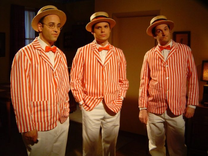 Three men wear red and white striped shirts, bow ties, and straw hats, as if they're in a barbershop quartet.