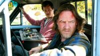 Hank, with cuts on his face, and Britt sit in Hank's truck, with some monitoring equipment on Britt's lap