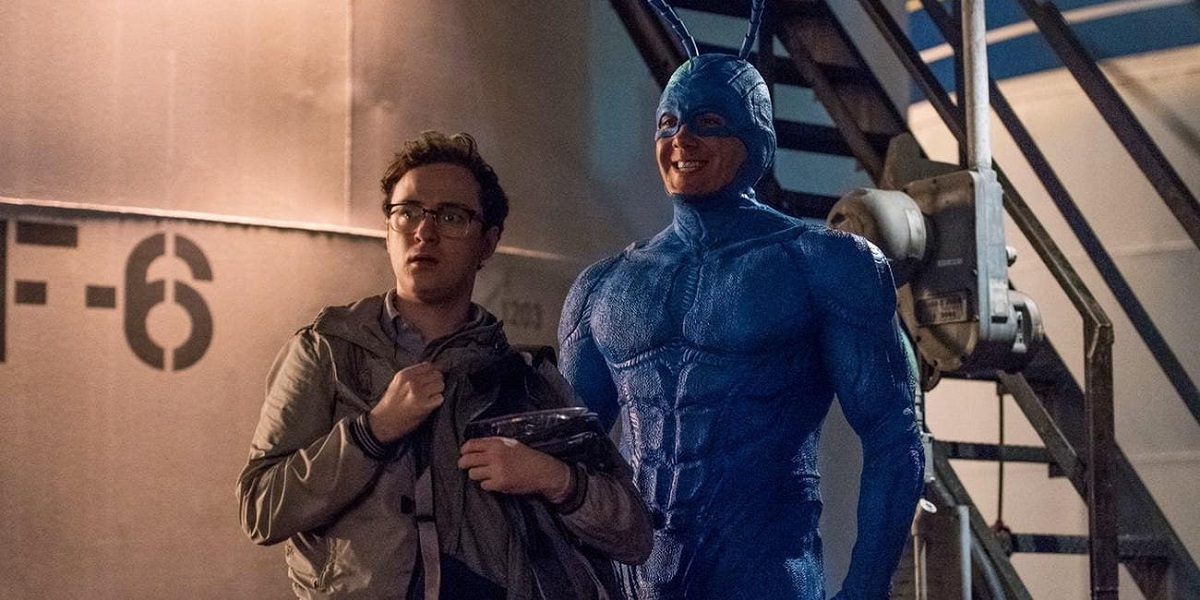 The Tick and Arthur (not in costume) stand together in an industrial area.