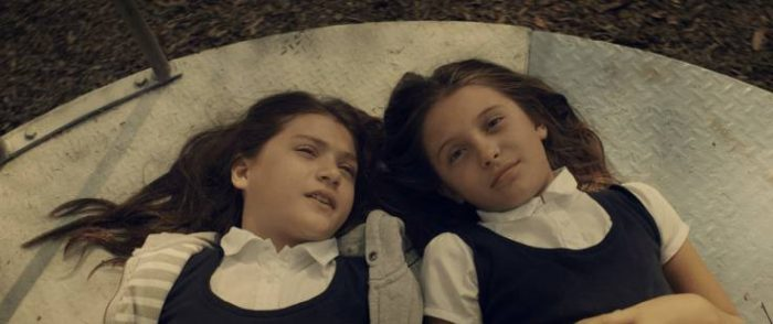 Young Lucie and Anna are laying on a merry-go-round, looking up at the sky.