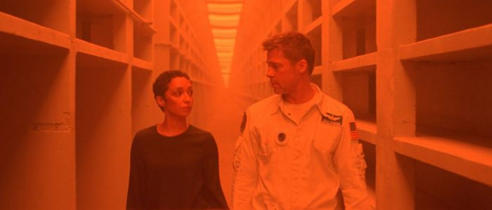 Helen Lantos and Roy McBride pass through an orange-lit hallway on subterranean Mars.