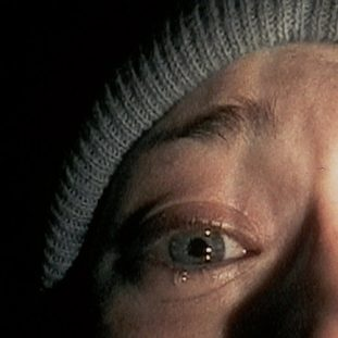 top half of a terrified womans face in torch light with a tear running down her cheek