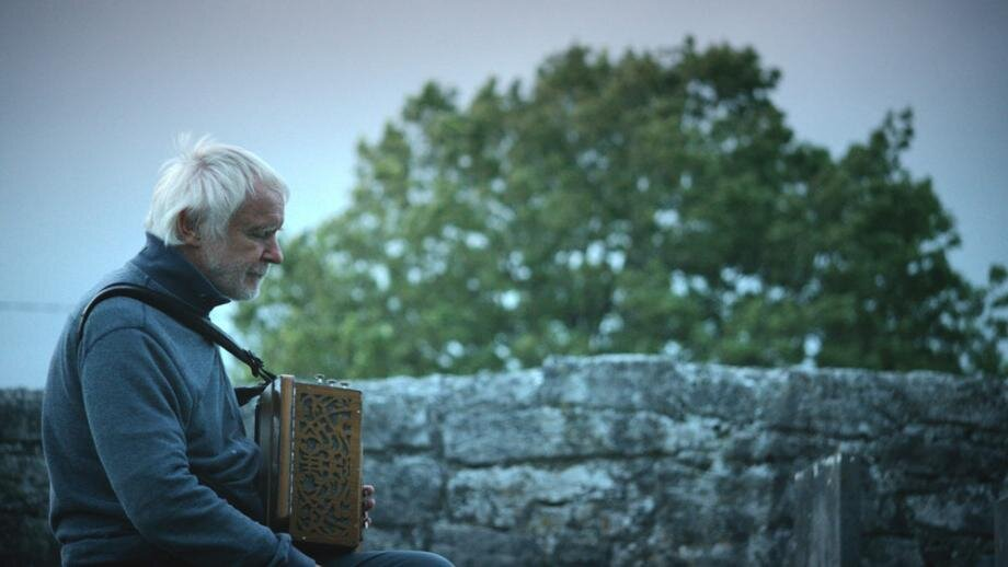 Máirtín O'Connor sits with an accordion in a Galway historical park