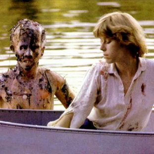 a woman in a canoe with the decomposed corpse of a boy behind her