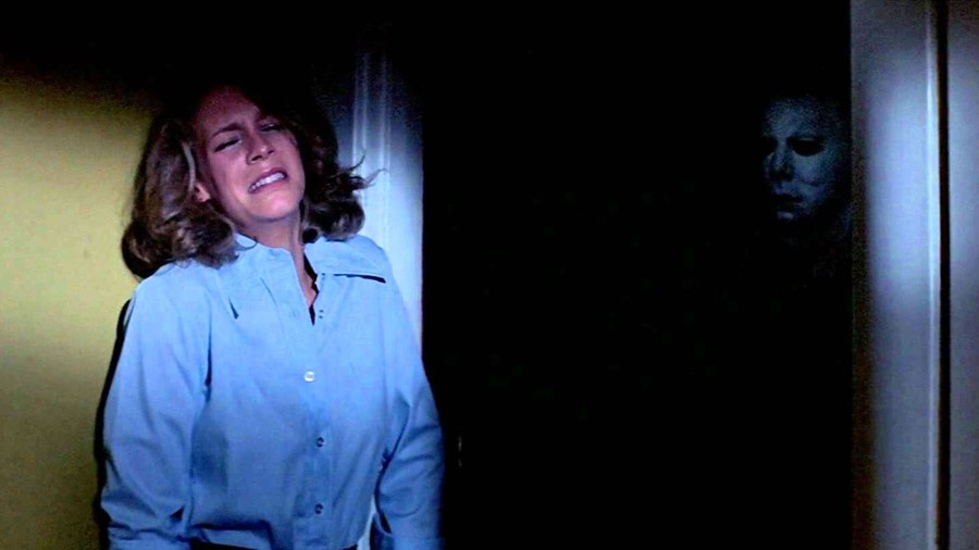 Jamie Lee Curtis as Laurie Strode in the original Halloween hiding from Mike Myers