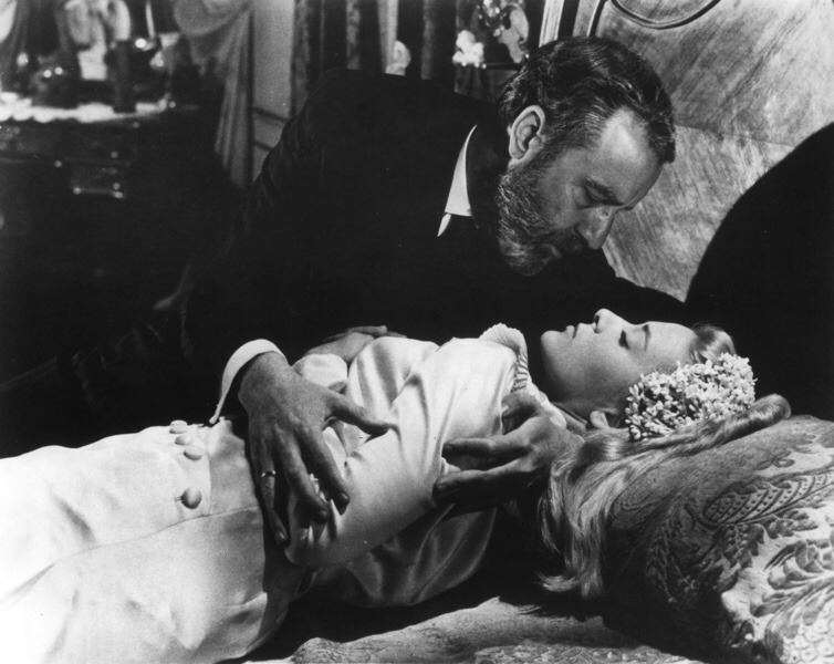 Don Jaime (Fernando Rey) takes advantage of a drugged Viridiana (Silvia Pinal), who is lying on a bed wearing his late wife's wedding dress.