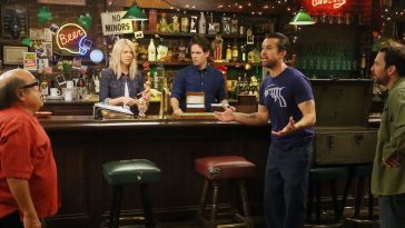Dennis, Dee, and Charlie stand in Paddy's Pub watching Mac yell at Frank