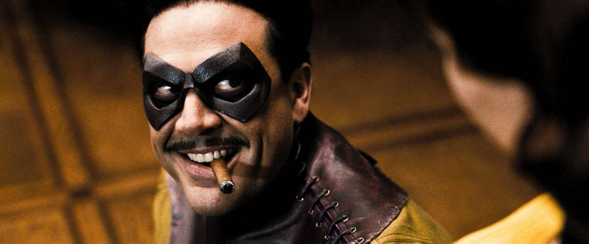 Image from the 2009 Watchmen film with close up of Comedian grinning with cigar in mouth looking up at Sally Jupiter.