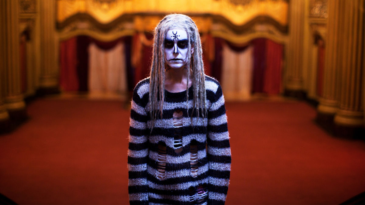 Girl with black and white striped sweater and painted goth black and white face in Lords of Salem