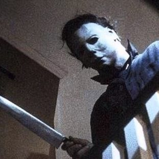 michael myers peers over the top of a staircase with a knife in his hand and mask on