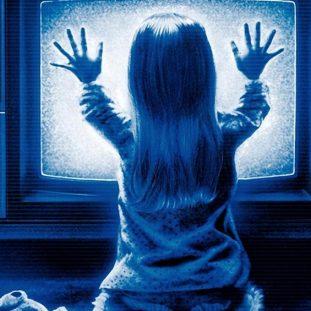 a little blonde girl put her hands up to a tv screen