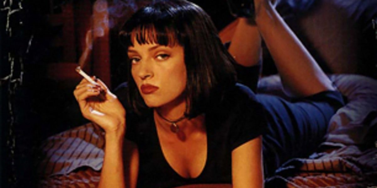 Uma Thurman laying on her stomach on a bed, cigarette in hand and heeled feet swinging in the air.