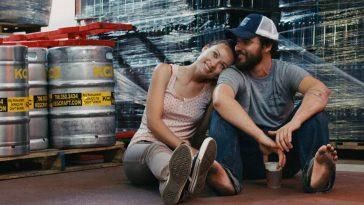 Kate (Olivia Wilde) puts her head on the shoulder of Luke (Jake Johnson) with a smile among the beer kegs of their shared workplace.