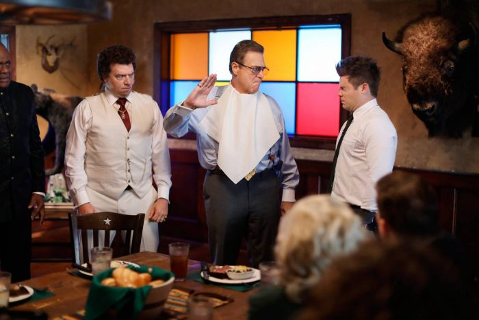 Standing behind a lavish dinner table, Eli (John Goodman) prepares to slap his son Kelvin (Adam Devine) as other son Jesse (Danny McBride) looks on.