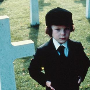 Damien from The Omen standing in a cemetary