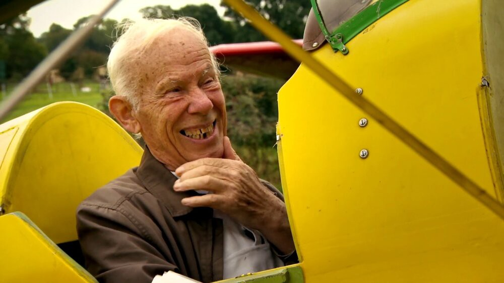 Bobby Coote smiles widely as he sits in a plane in The Man Who Wanted to Fly