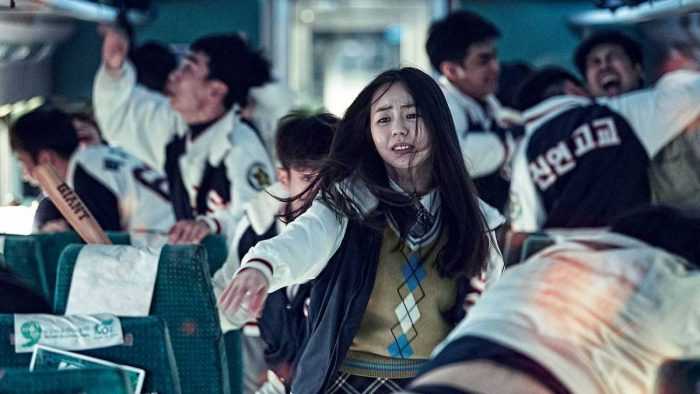 A female Korean student is surrounded by zombies on a train.
