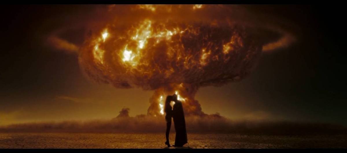 Dan and Laurie embrace in front of a nuke going off